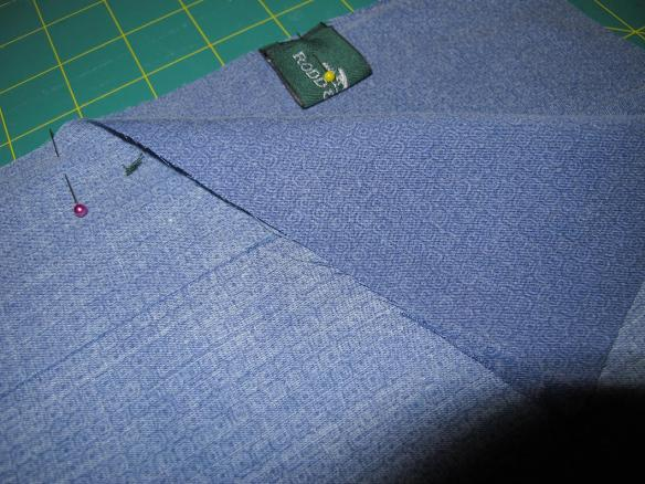 Step 4: Now flip one of the pieces over and place the two pieces right sides together. Adding the tags into the seamline if you like, folding them inhalf and matching the raw edges.