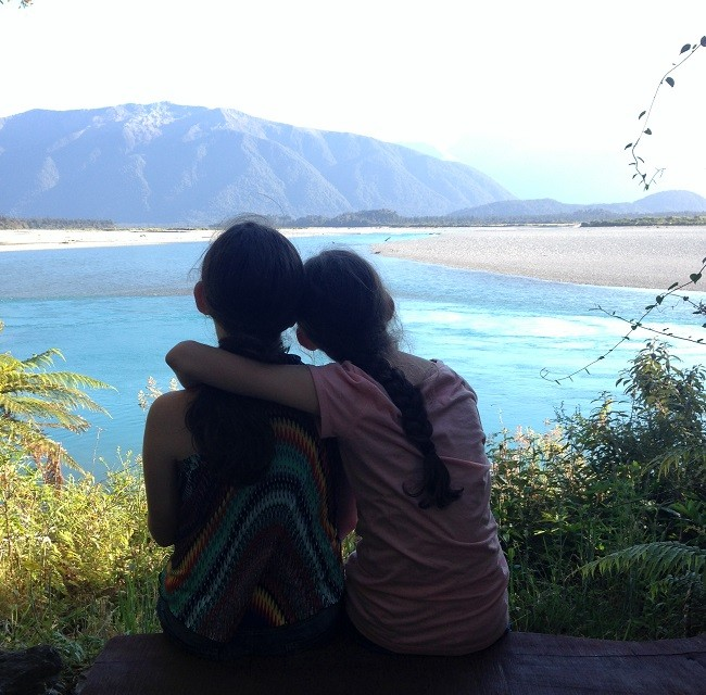 The girls sitting by the Haast River, New Zealand
